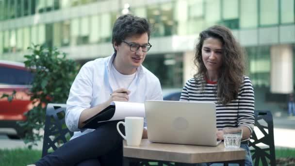 Mladí podnikatelé se o jejich projektu ve venkovní kavárně