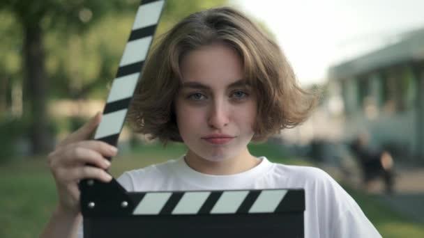 Vážné mladá herečka při pohledu na fotoaparát, po klapka používá