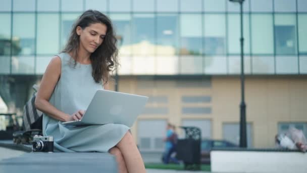 Gyönyörű fiatal nő kamera gépelni rajta laptop felhőkarcoló közelében ült