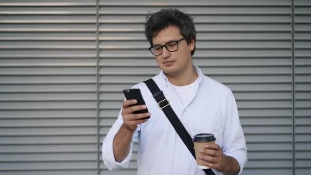 Pohledný mladý podnikatel při pohledu na smartphone stojí venku s kávou