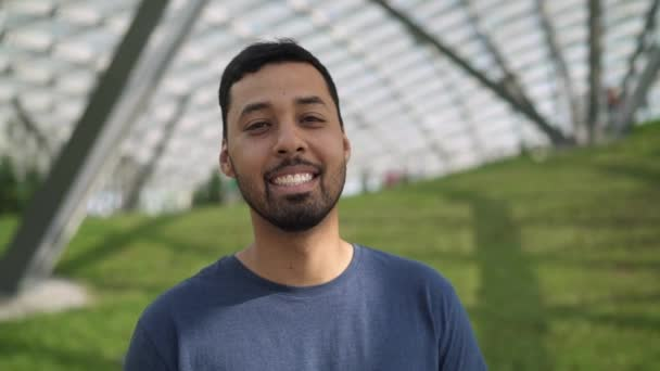 Pohledný mladý muž při pohledu na fotoaparát a usmívá se stojící mimo