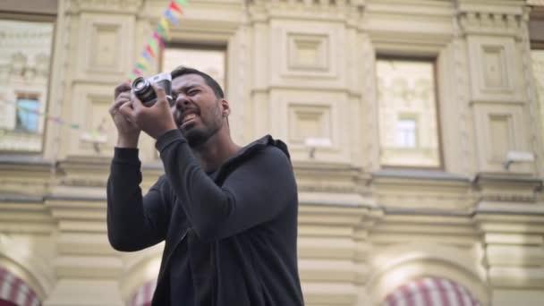 Veselý mladý turista natáčení hledí s kamerou