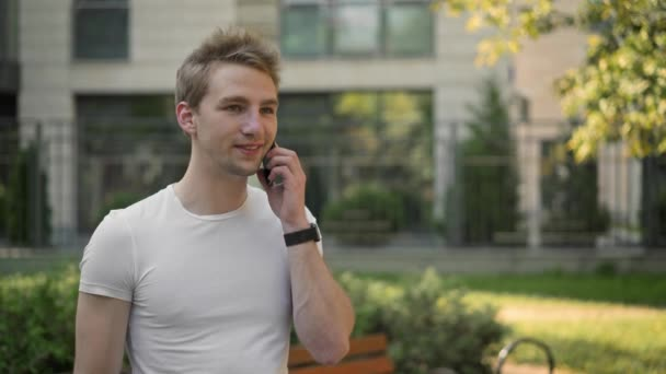 Side view of young man talking on phone outside