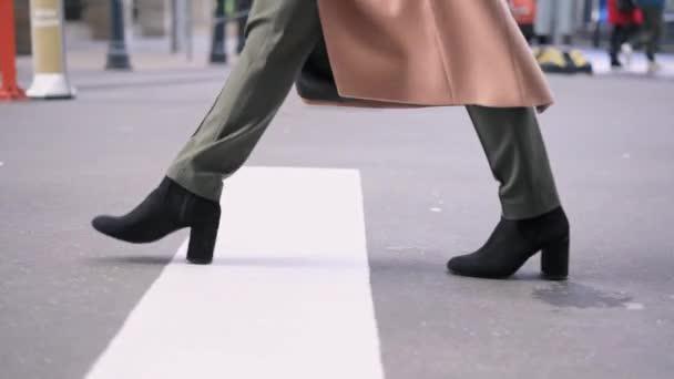 Nohy ženy v černých botách přes silnici
