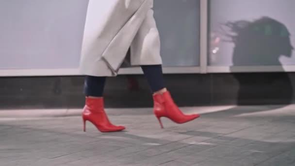 Nohy žena nosí černé kalhoty, bílý plášť a červené boty chůze v ulici na podzim. Sledování zpomalené průměrný střelec