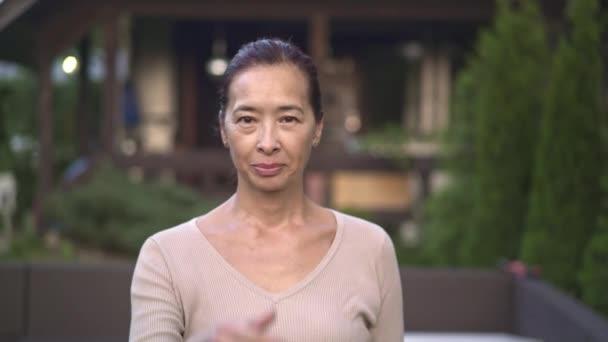 Středního věku Asijské žena ukazuje palec nahoru venku
