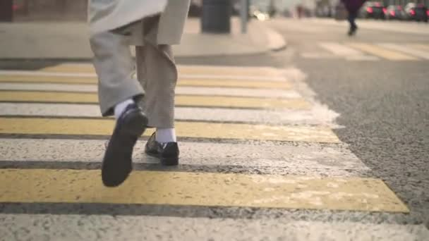 Legs of woman in black boots crossing the road on a crosswalk