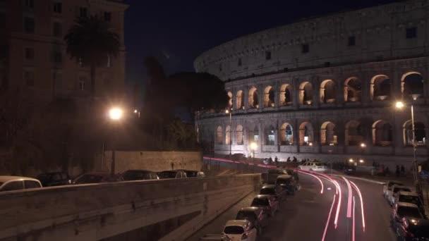 Balról jobbra Timelapse pán lövés a Colosseo, Róma közeli éjszakai forgalom. A Colosseum is ismert, mint a FLAVIÁN amfiteátrum. Egy ovális amfiteátrum a város Róma központjában