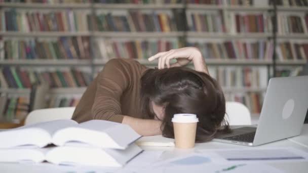 Egy fáradt férfi diák elaludni a könyvtárban