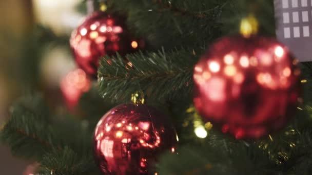 Tilt up shot of christmas tree with red christmas balls