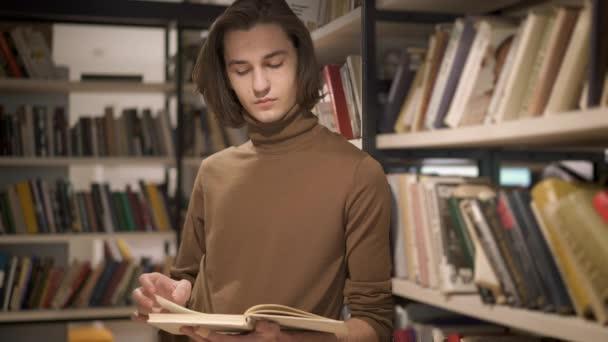 A fiatalember a lapozható könyv a könyvtárban könyvespolcokat között