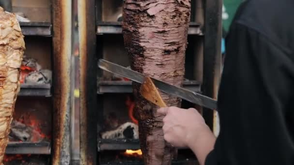 A cook cuts beef to make shawarma, gyros, doner kebab. Cooking meat on a skewer