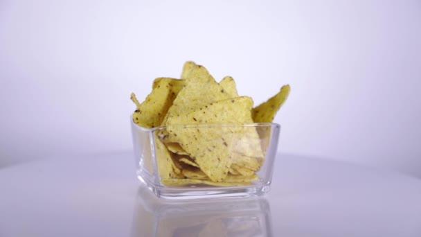 Malá hromádka nachos v malé průhledné čtvercové skleněné nádobě