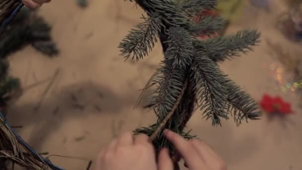 Child and adult hands winding up christmas tree branches making a wreath