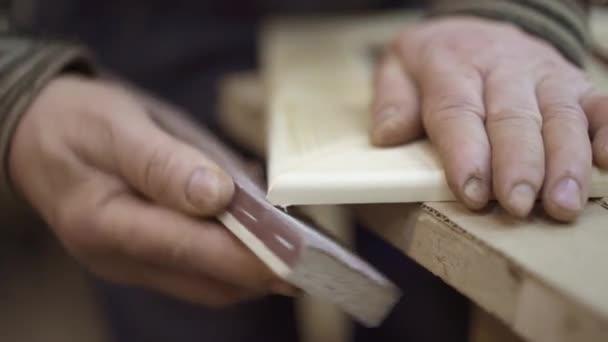 Man sanding wood frame with sandpaper in woodcraft studio