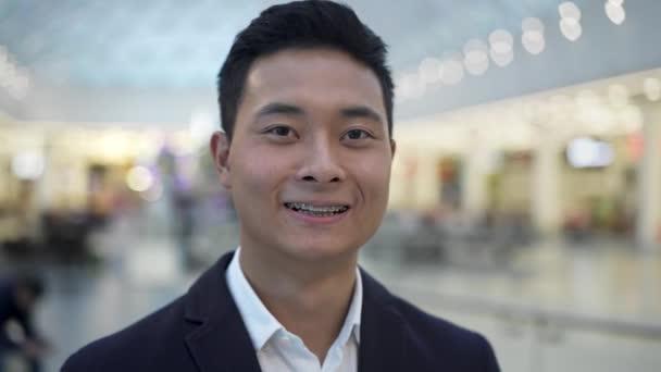 Nahaufnahme Porträt eines asiatischen Mannes mit Zahnspange, der lächelnd in die Kamera schaut