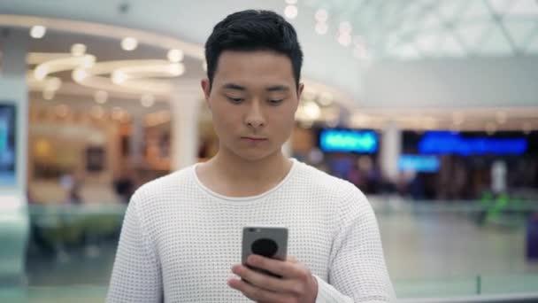 Pomalý pohyb asijského muže chůze s telefonem na rozmazané pozadí