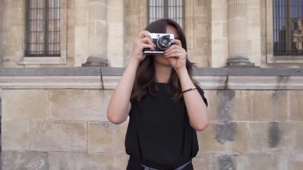 fröhliche junge Frau mit dunklen Haaren im schwarzen T-Shirt, die Fotos macht. Porträtaufnahme in Zeitlupe.