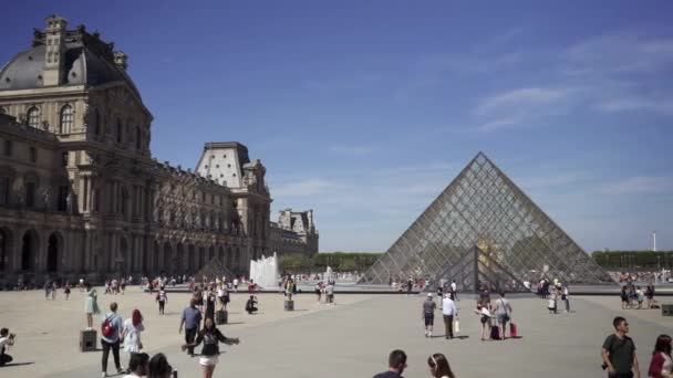 PARIS - June 17 2019: Real time establishing shot of Tourists walk in front of the Louvre. The Louvre Museum is one of the most visited art museum in the world.