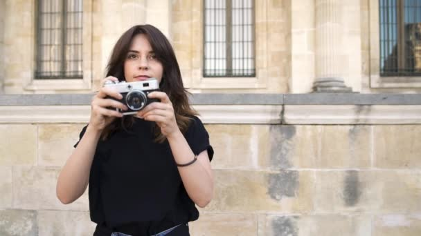 Paris, Frankreich hübsche Frau macht Foto mit einer Filmkamera. alte Gebäude in Paris im Hintergrund