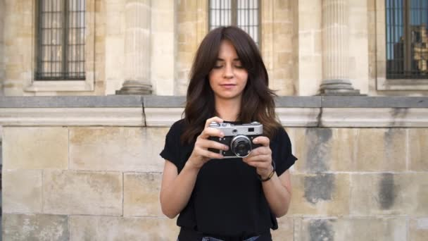 junge Frau beim Fotografieren einer Filmkamera. alte Gebäude in Paris im Hintergrund