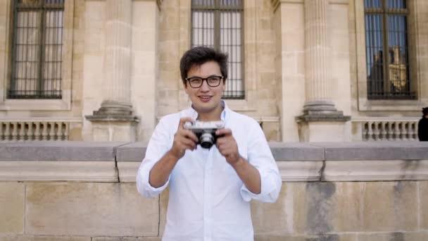 Pohledný muž v bílé košili s obrázkem pařížské architektury