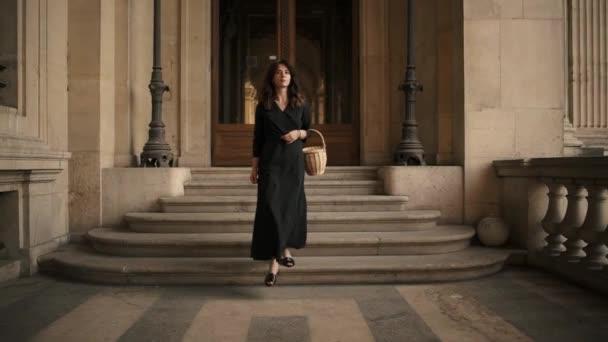 Pomalý pohyb atraktivní ženy v černých šatech po pařížských ulicích ve Francii