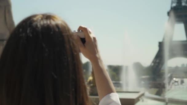 Pan záběr zpět elegantní žena dělat fotografii Eiffelova věž s filmovou kamerou
