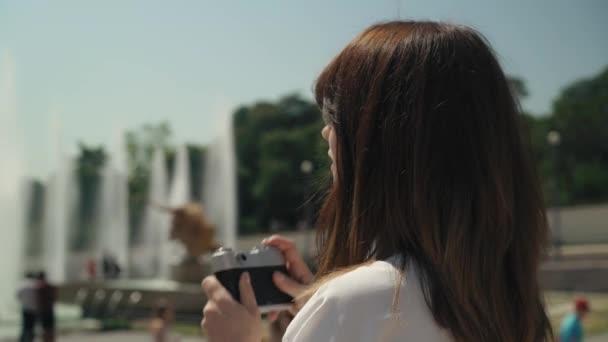 Kruhový snímek elegantní ženy, jak fotografuje Eiffelovku s filmovou kamerou