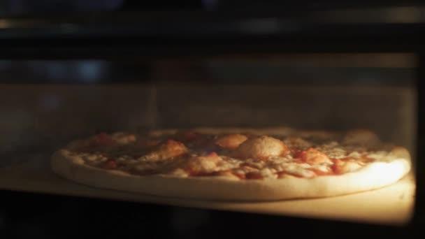Ruční zblízka pohled na pečení sýrové pizzy v troubě