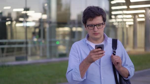 Vorderseite rechts Mitte Aufnahme eines jungen Mannes, der im Freien sein Handy eintippt
