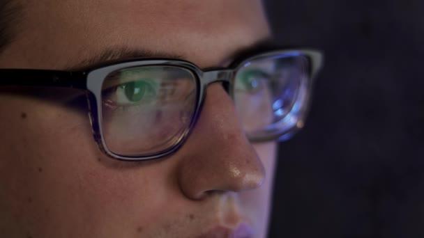 Muž v brýlích pozdě v noci rolování před notebookem
