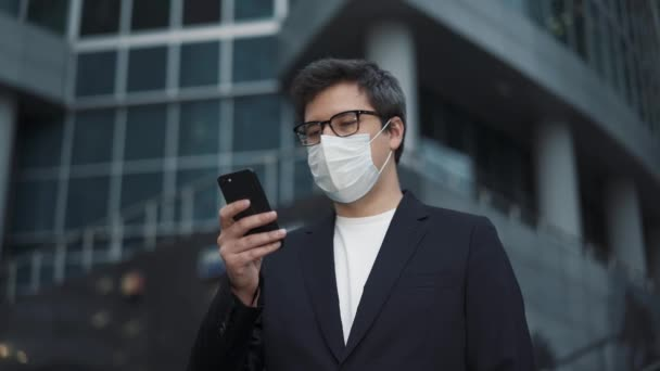 Businessman wearing a protective mask holding a phone near business centre