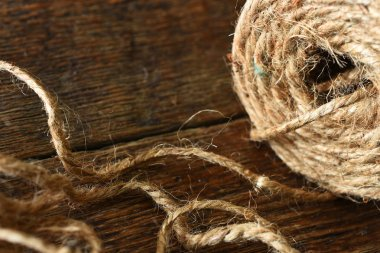 A close up image of old fashioned brown packing rope on a wooden table top.