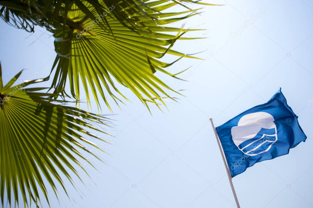 Blue Flag against blue sky. Blue Flag is an international award given to beaches that meet excellence in the areas of safety, cleanliness and environmental standards.