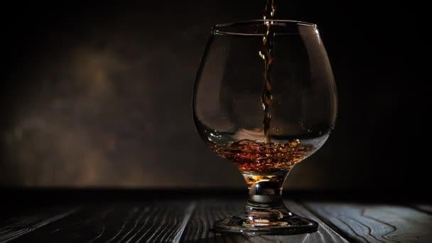 Cognac öntenek egy pohárba. Sötét háttér.