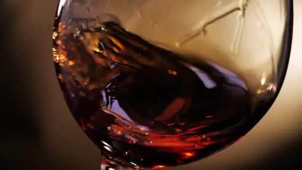 Cognac van forgatva egy pohár. Sötét háttér.