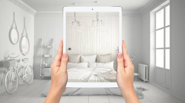 Hands holding tablet showing modern scandinavian bedroom, total blank project background, augmented reality concept, application to simulate furniture and interior design products