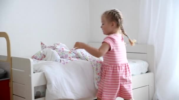 A girl of 3 years old makes a bed in the children room