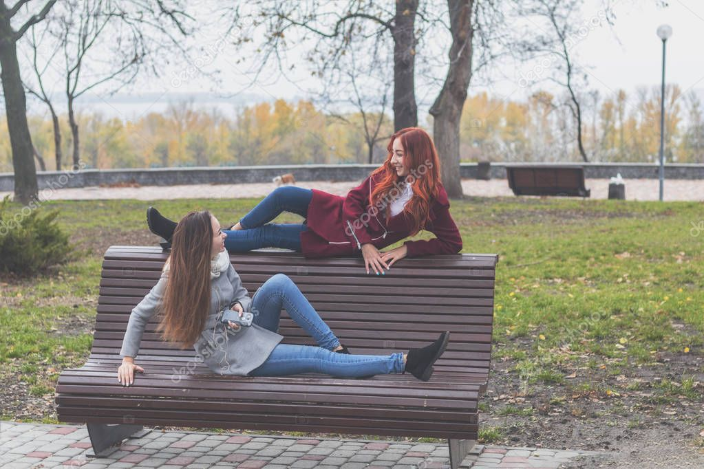 Two happy cute beautiful female teenagers at the bench in an autumn city park