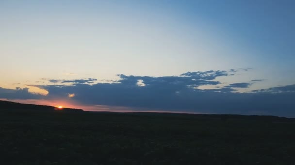 Field and forest in the amazing beautiful clorfull summer sunset. Beautiful thunder clouds over the field, shooting from a car that goes on the road along the ground. Evening, Dynamic scene, 4k video