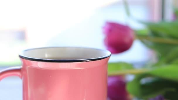 Heißen kochen Tee in Rosa Keramik Tasse mit Paaren auf der Fensterbank, Rosa Tulpen in der Nähe von Tasse Tee