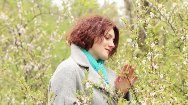Docela romantické mladá červená hlava žena s třešňovou větví květy na jaře parku. Jarní stromy pozadí. Portrét zblízka.
