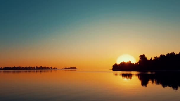 Amazing beautiful sunrise sky over calm smooth river surface. Summertime, dynamic scene, 4k video.