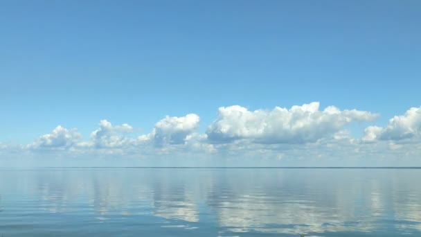 Amazing beautiful blue sky with light white clouds over calm smooth river surface. Summertime. Sunny day. Time-lapse HD video.