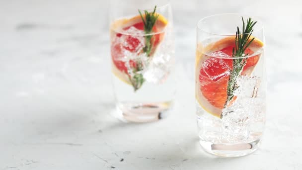 Alkoholischer Cocktail mit Grapefruit, Limonade, Eis, Gin und Rosmarin, hellgrauer Betontischhintergrund, selektiver Fokus, geringe Schärfentiefe.