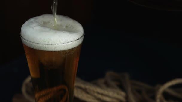 Nalil řemesla pivo z láhve do pití skla na tmavém pozadí zblízka. Sllow motion full hd video