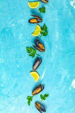 Mussels, lemon, parsley on blue concrete table
