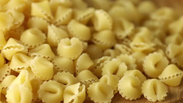 Italian raw uncooked pasta sorprese on wooden table. Pile of raw italian pasta rotating in circle.