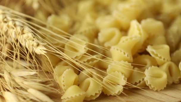 Italian raw uncooked pasta sorprese on wooden table. Motion video. Concept of healthy eating